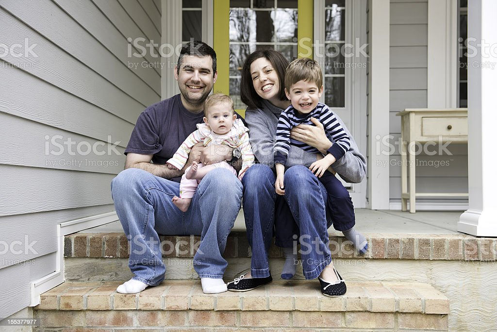 Candid portrait of family sitting on front porch stairs stock photo