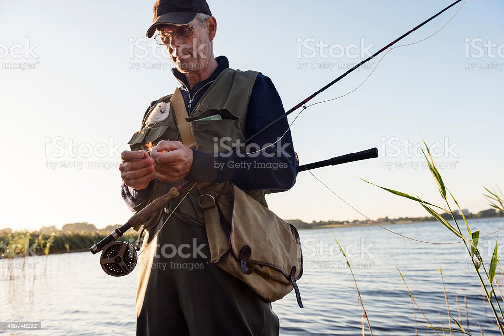 Candid Portrait of Fly Fisherman Tying a Fly stock photo