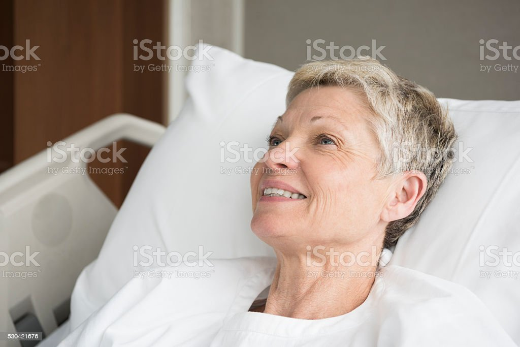 Candid portrait of smiling senior woman in hospital bed stock photo