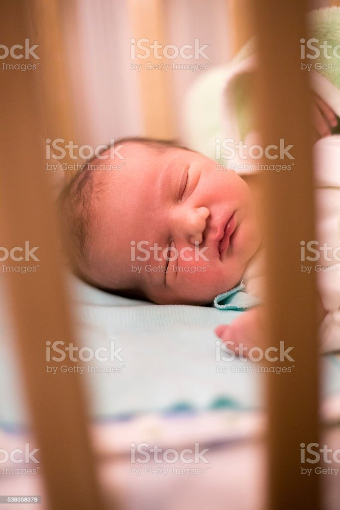 Candid portrait of  white Caucasian newborn sleeping in his crib stock photo