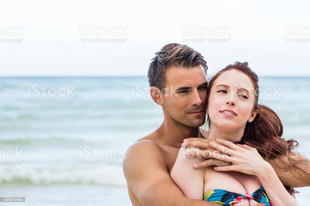 Candid portrait of young couple embracing love on beach; hug stock photo