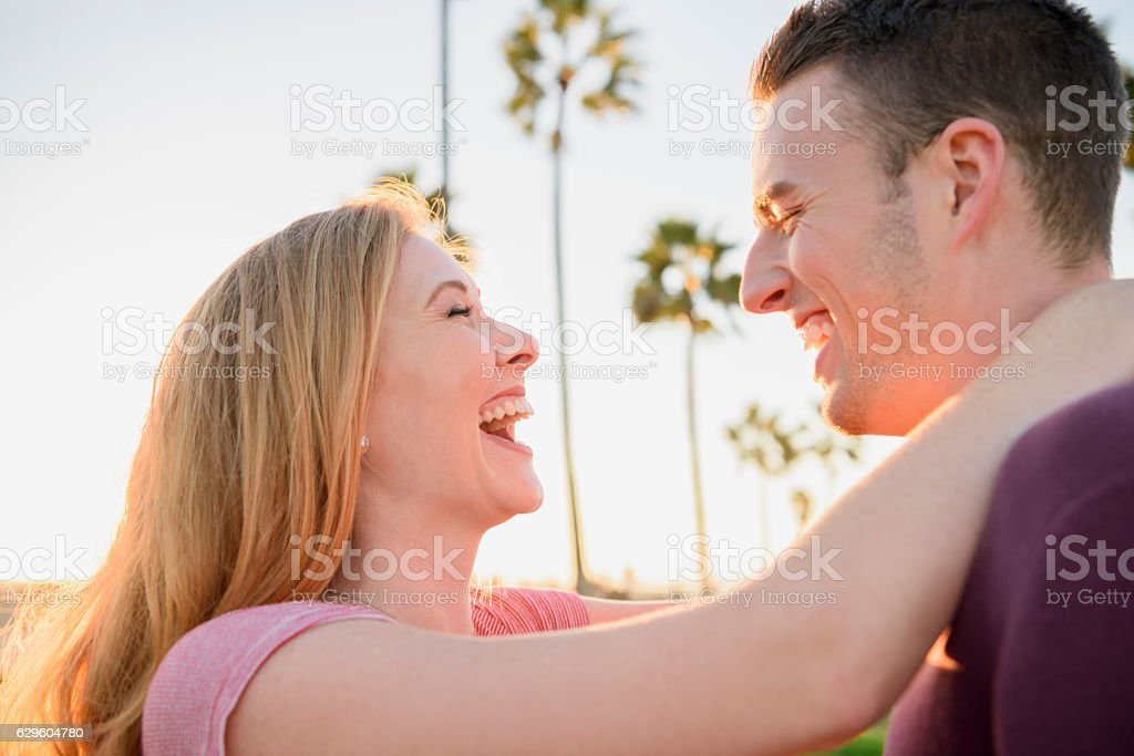 Candid portrait of young couple laughing outside in sunlight stock photo