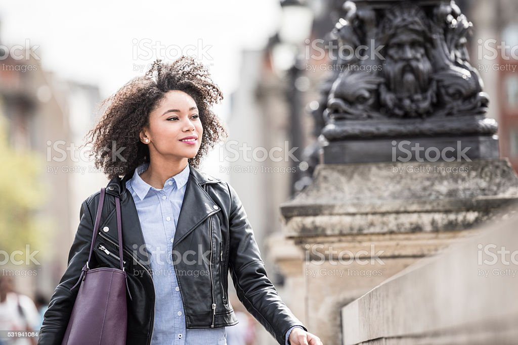 Candid portrait of young woman with black leather jacket stock photo