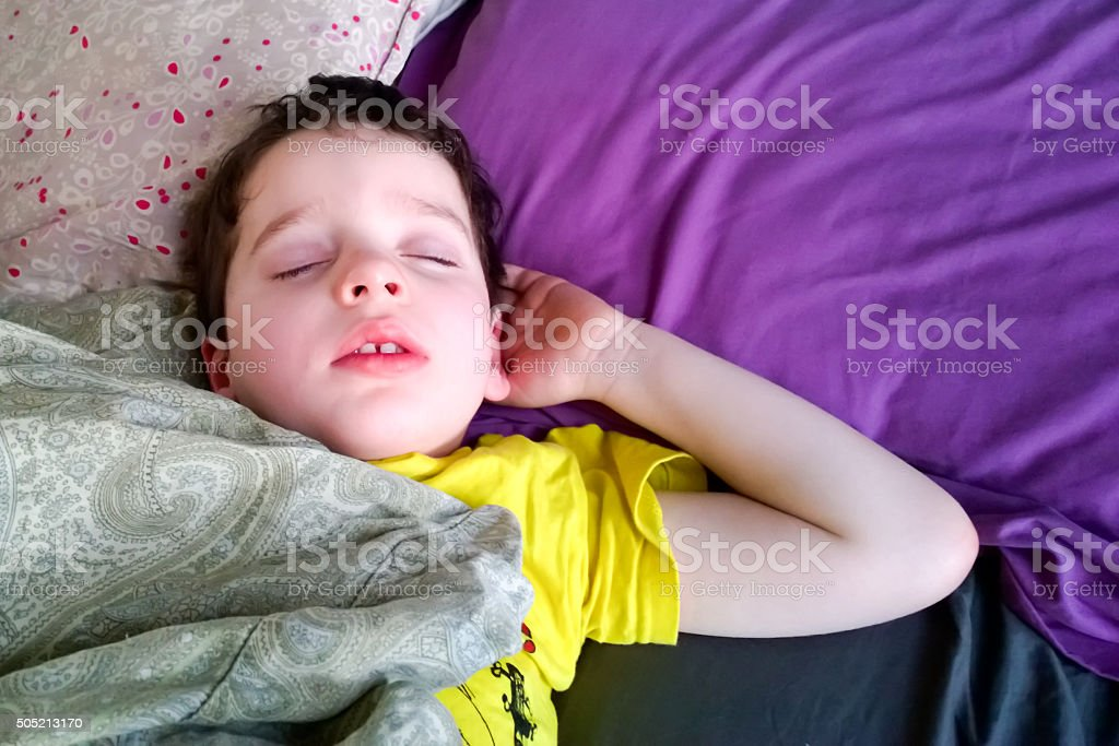 Candid pose of young child sleeping in bed stock photo