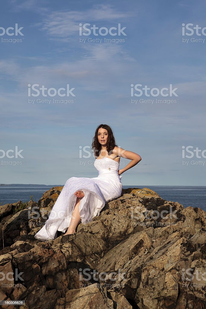 Candid shot of bride on rocky outcropping royalty-free stock photo