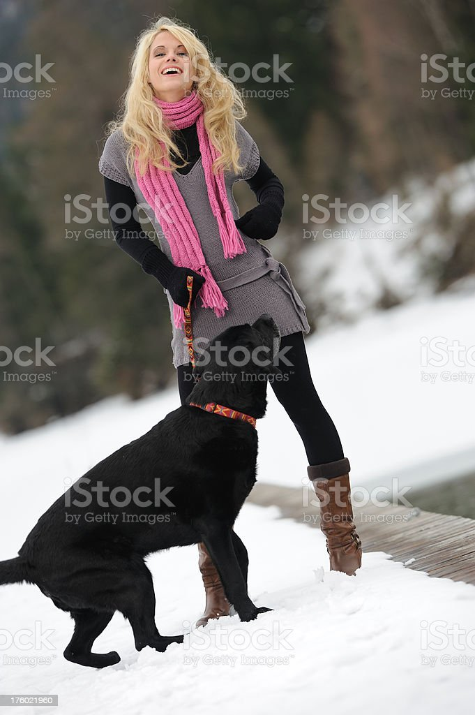 Candid Smiling Girl playing with her Dog in the Snow royalty-free stock photo