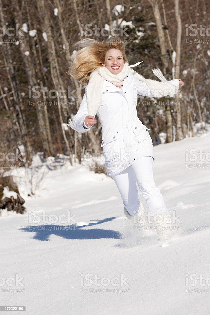 Candid Winter Fun, Beautiful Woman running through the Snow royalty-free stock photo