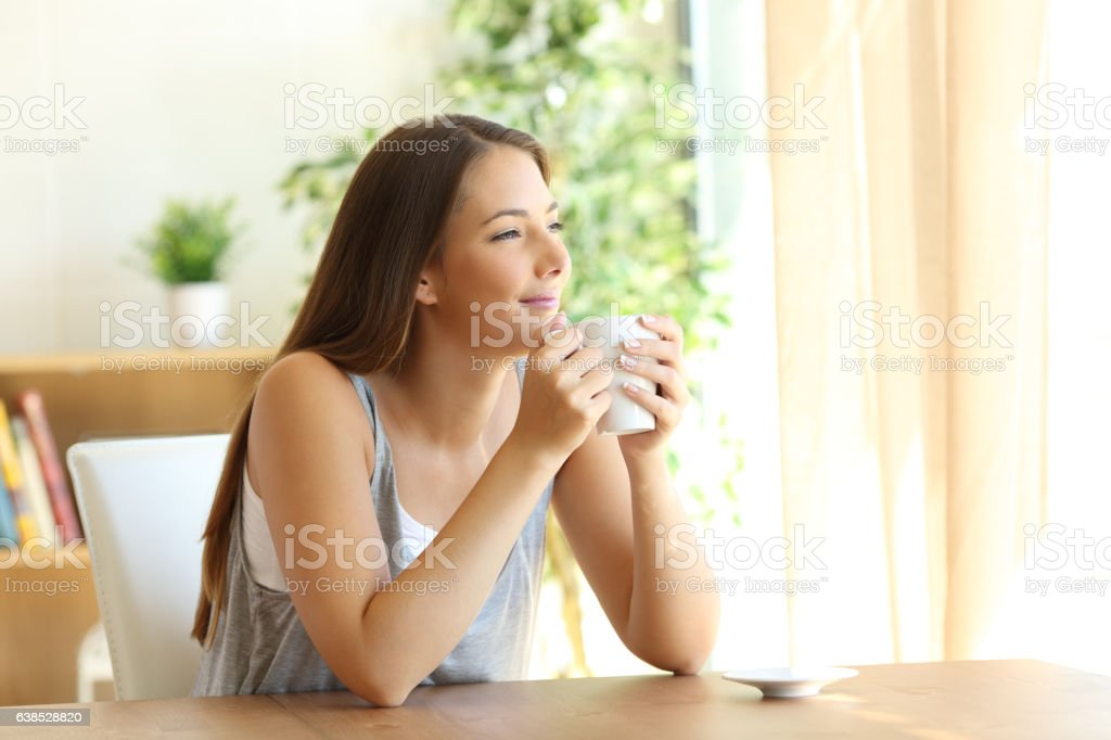 Candid woman thinking at home stock photo