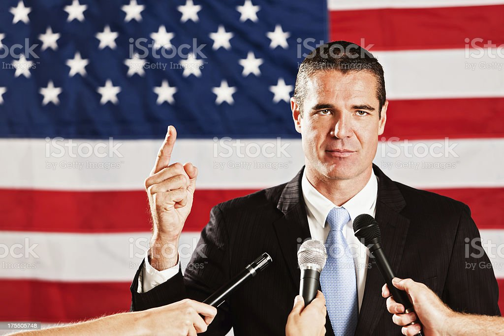 Candidate by US flag responding to press questions at interview stock photo