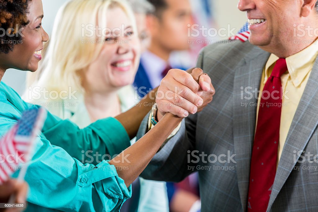 Candidate shaking supporter's hand during local political rally stock photo