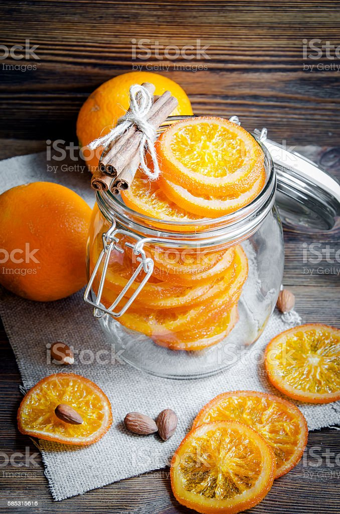 Candied oranges in jar, cinnamon and almond stock photo