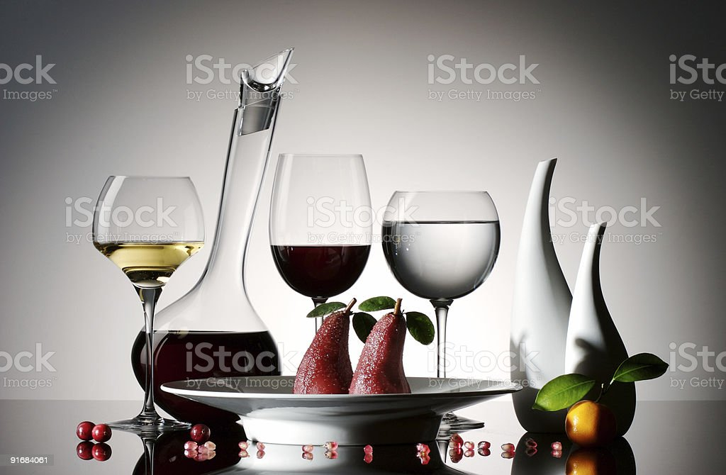 Candied pear in red wine with glasses and decanter stock photo