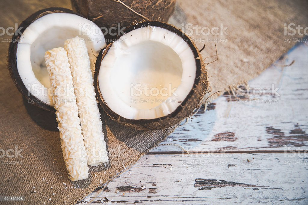Candies in coconut flakes and fresh coconut stock photo