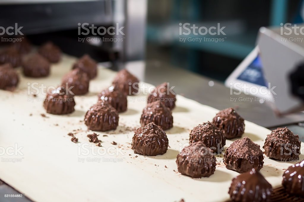 Candies with shavings on conveyor. stock photo