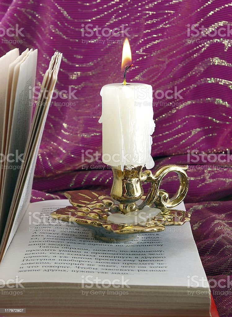 Candle and book stock photo