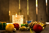 Candle and Christmas's ornament on wooden background