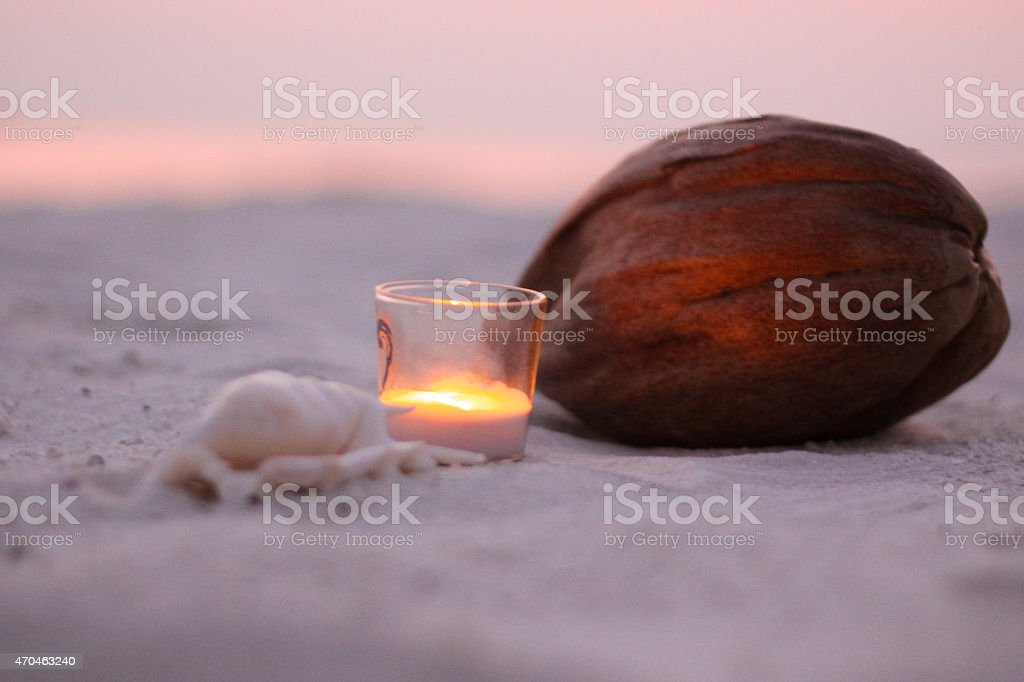 Candle and Coconut on the Beach stock photo