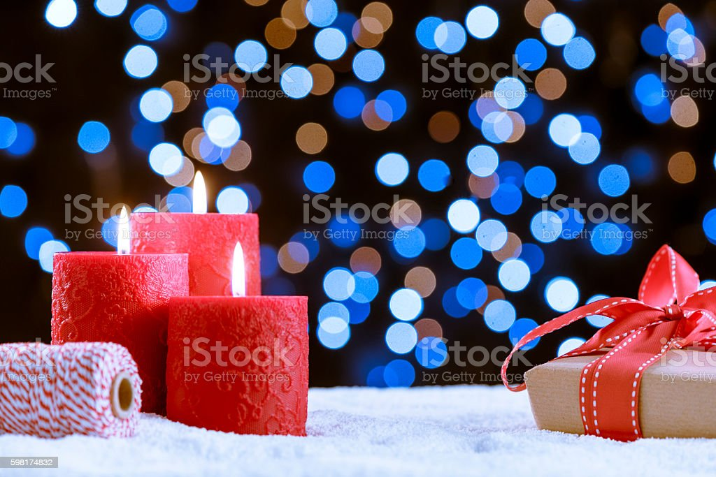 Candle and gift over snow for Christmas stock photo