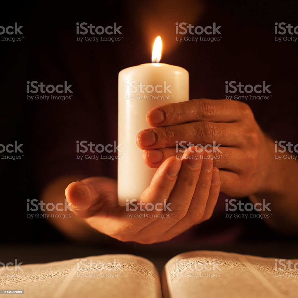 candle and hands (on a dark background, the Bible) stock photo
