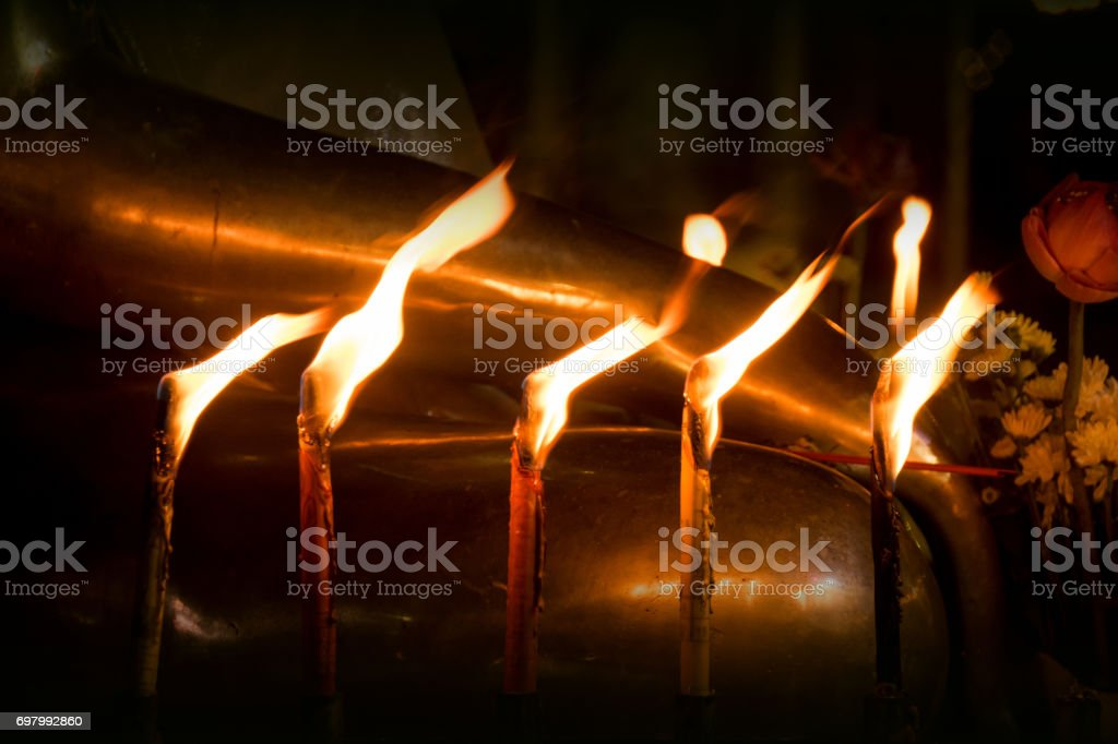 Candle and light on the front Buddha statue in night time stock photo