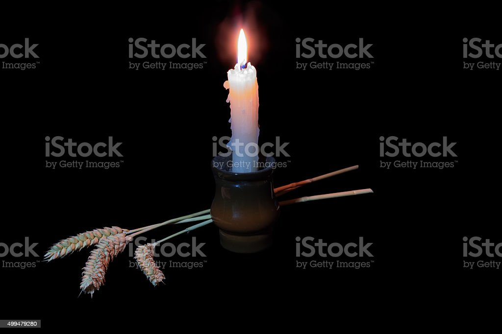 Candle and three ears on a dark background stock photo