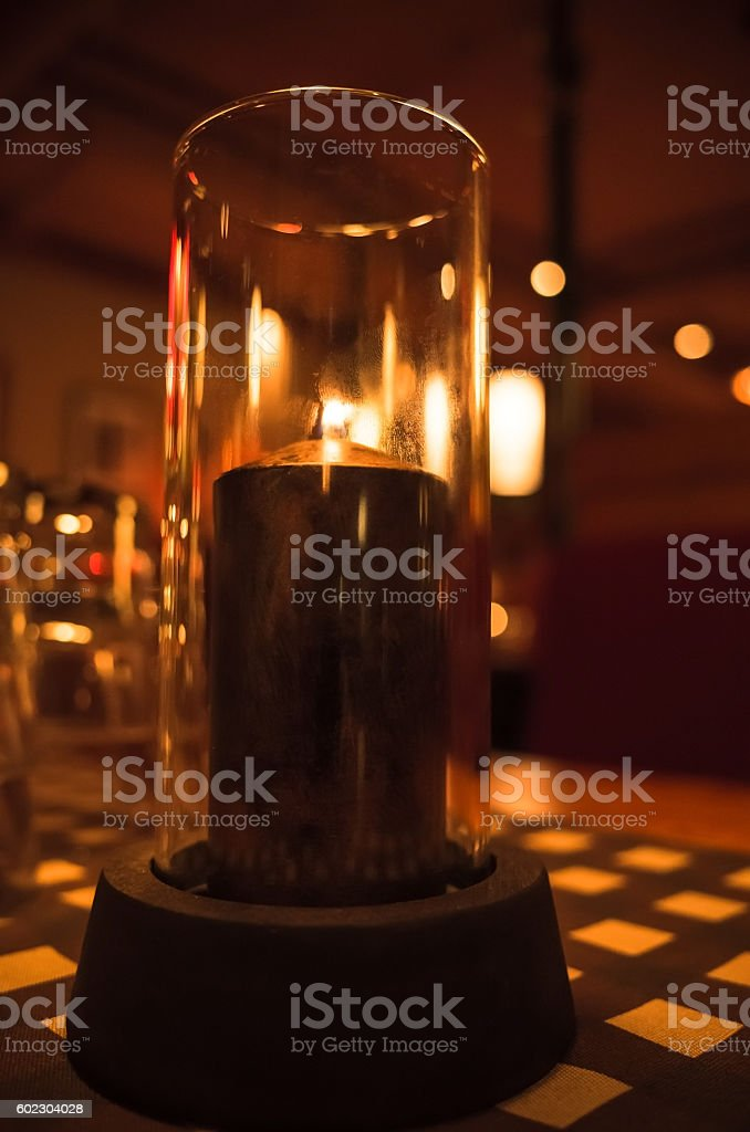 Candle burns in candlestick made of glass stock photo