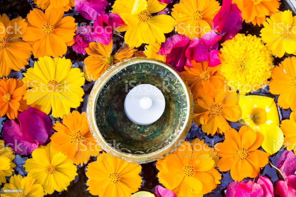 Candle Floating in a Foot Bath of Flowers in Thailand stock photo