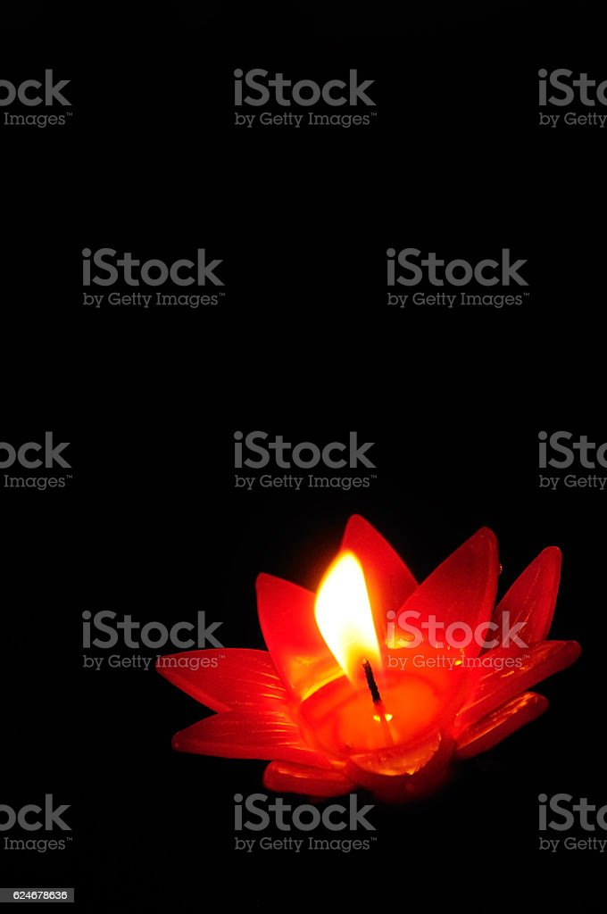 Candle floating on water with dark background stock photo