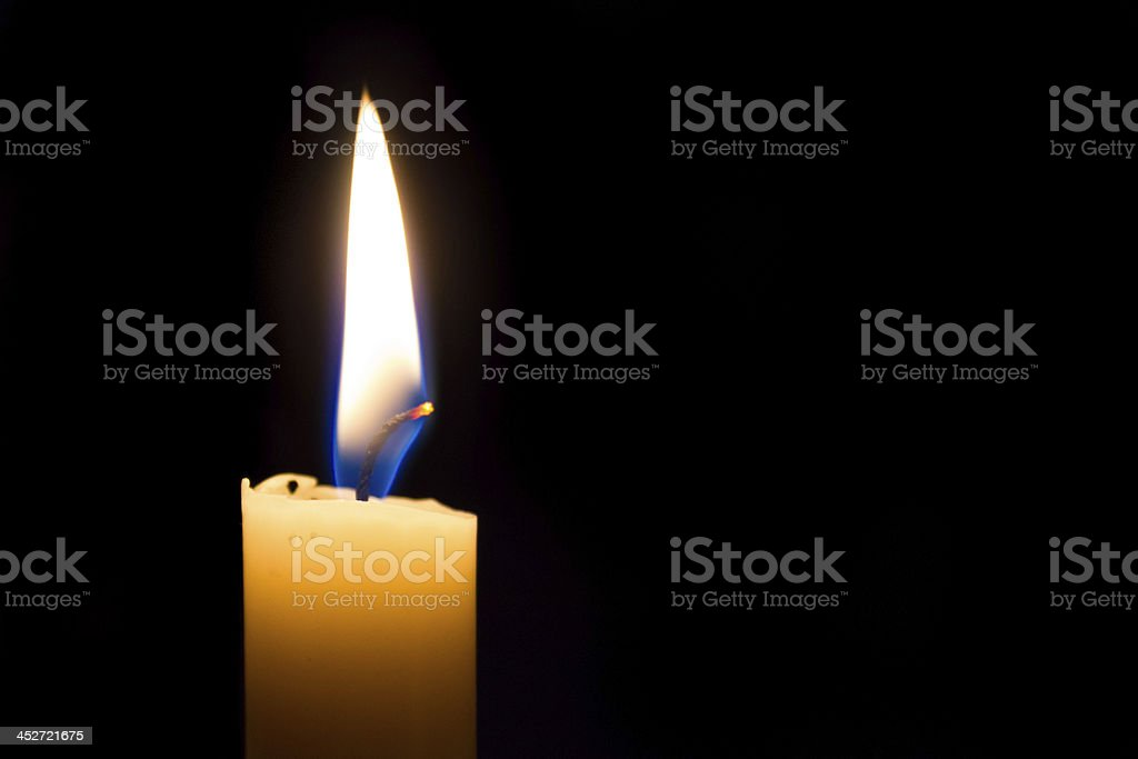 Candle glowing brightly in the dark stock photo