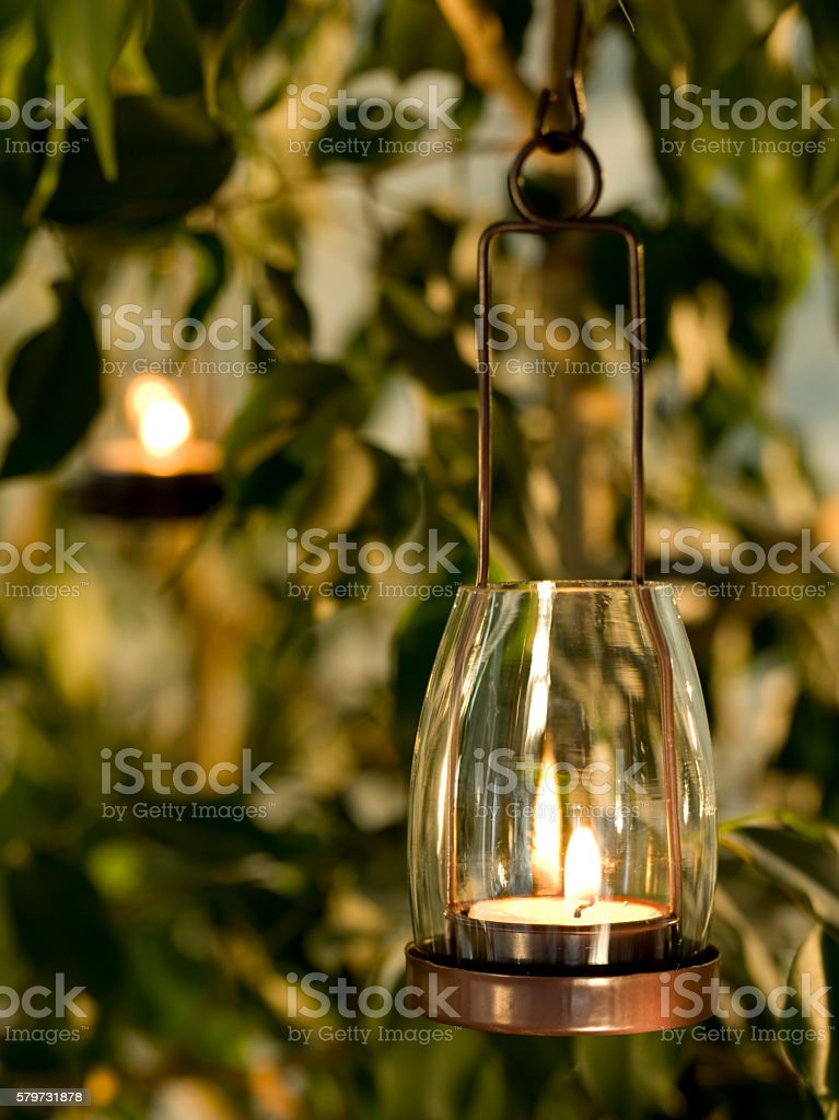 Candle hangs in the garden stock photo