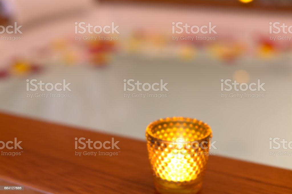 Candle in a glass candle holder near jacuzzi. Abstract blur background with bokeh stock photo