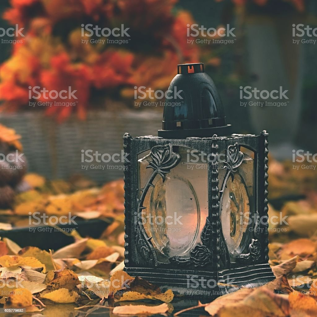Candle in a lantern on the grave. Background for Halloween. stock photo