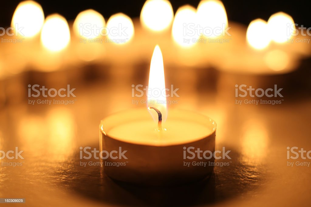 Candle in front of a group of candles stock photo