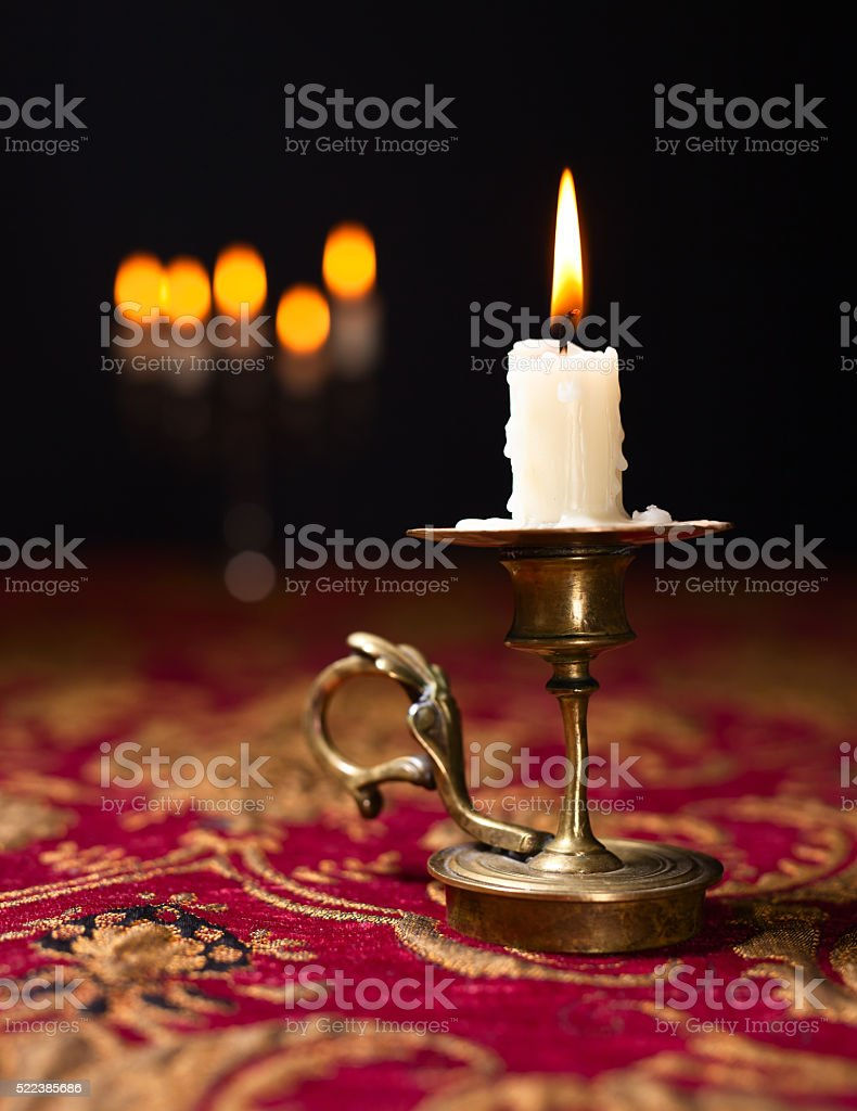 Candle in small brass candlestick stock photo