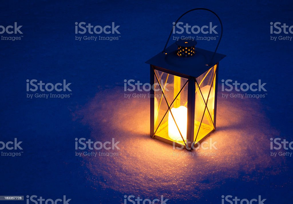 Candle lamp isolated in snow at night stock photo