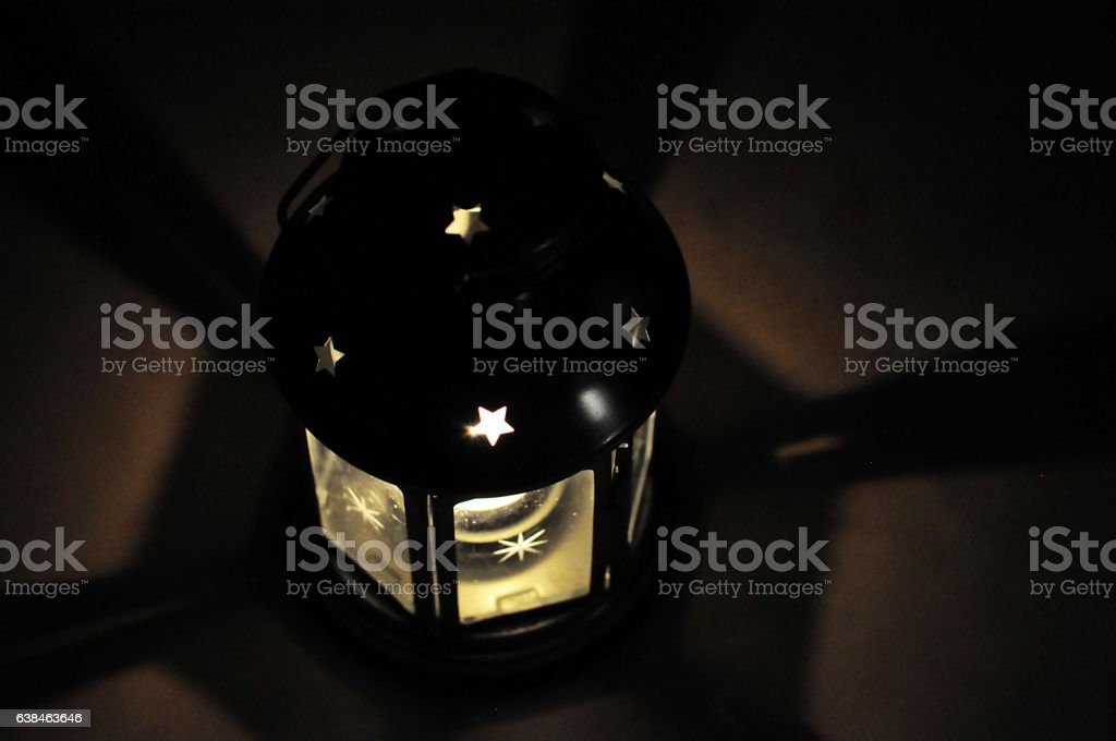 Candle lantern in dark with shades, shining star stock photo