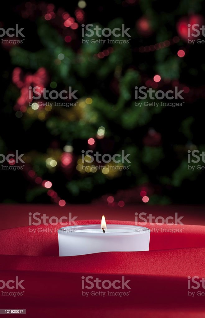 Candle light and defocused xmas tree lights royalty-free stock photo