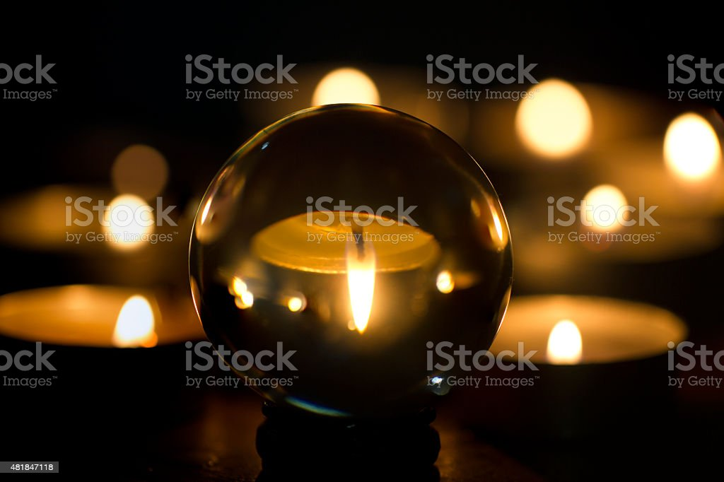 Candle light in Dark Behind Glass ball stock photo