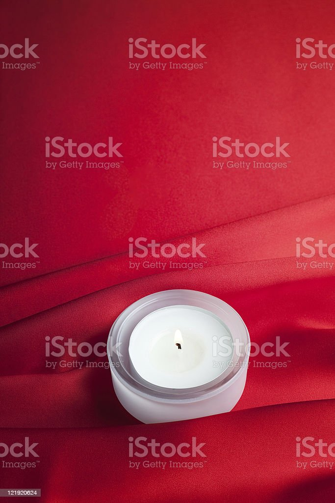 Candle light on red silk background stock photo