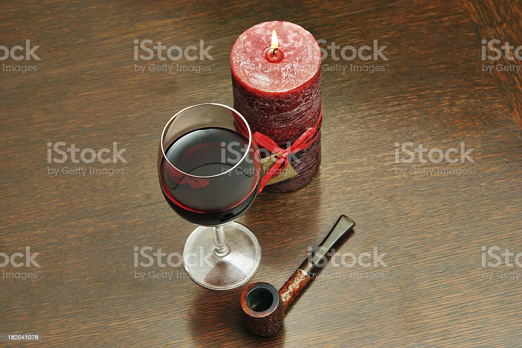 Candle lit wine and pipe. royalty-free stock photo