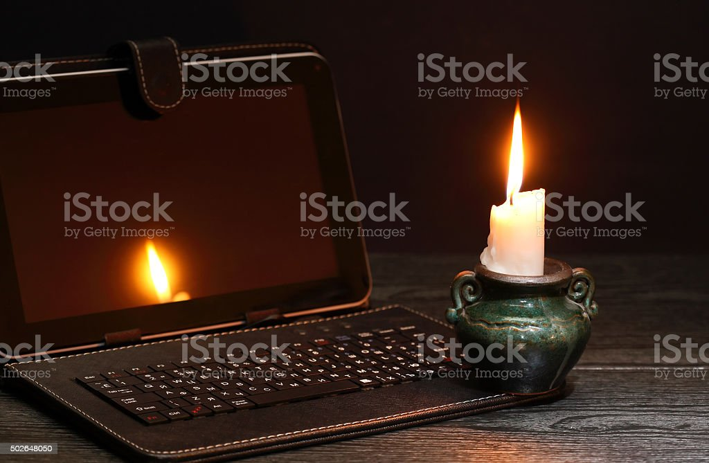 Candle Near Laptop stock photo