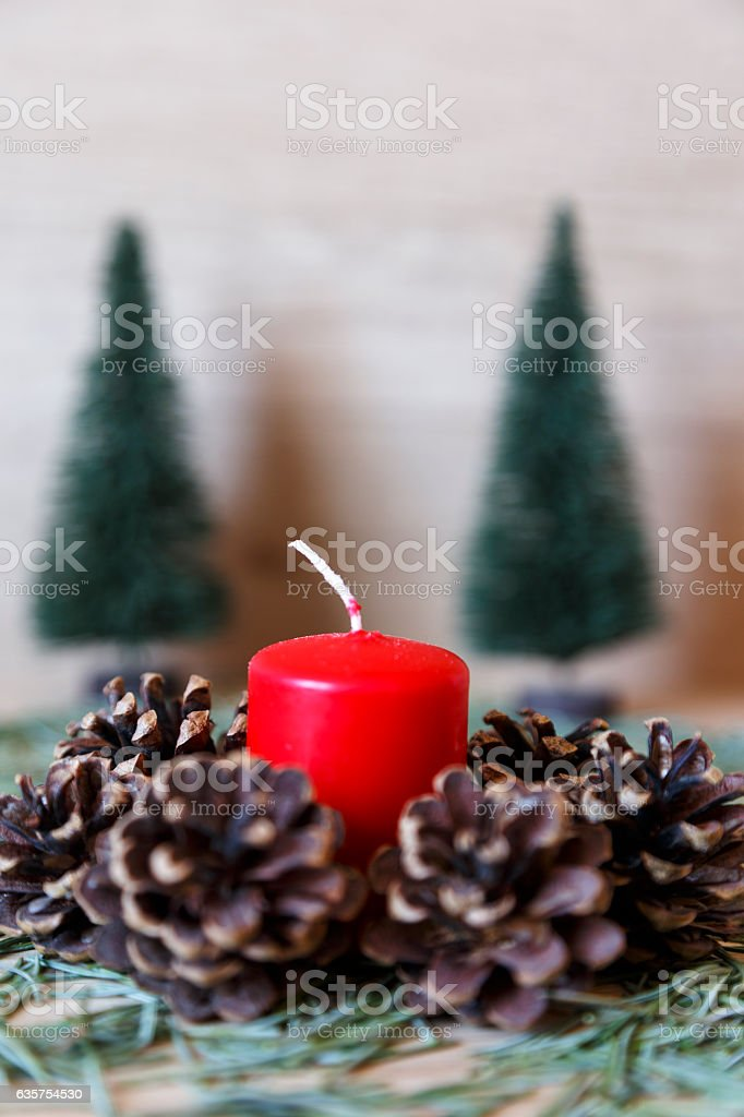 Candle next to set of pine cones as christmas decoration stock photo