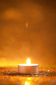 Candle on gold glitter with yellow background