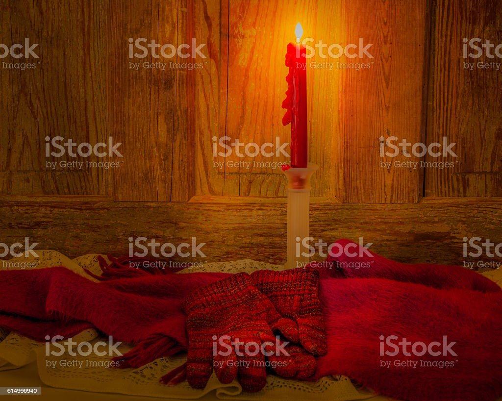 Candle, scarf  and gloves glow in candlelight against wood (P) stock photo