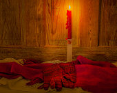 Candle, scarf  and gloves glow in candlelight against wood (P)