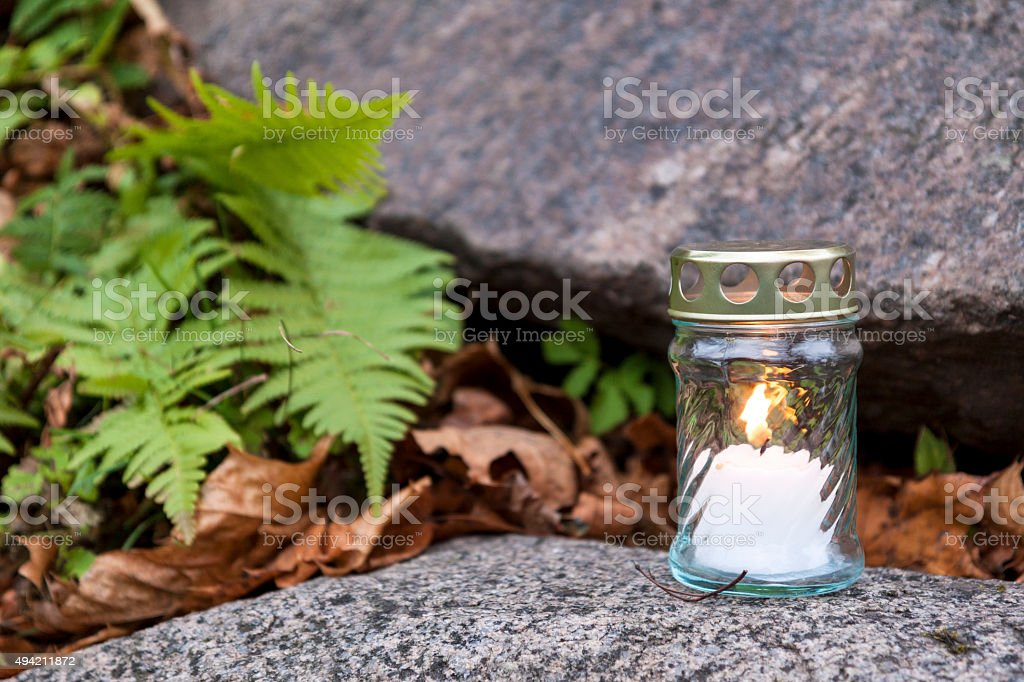 Candle standing on tombstone and burning stock photo