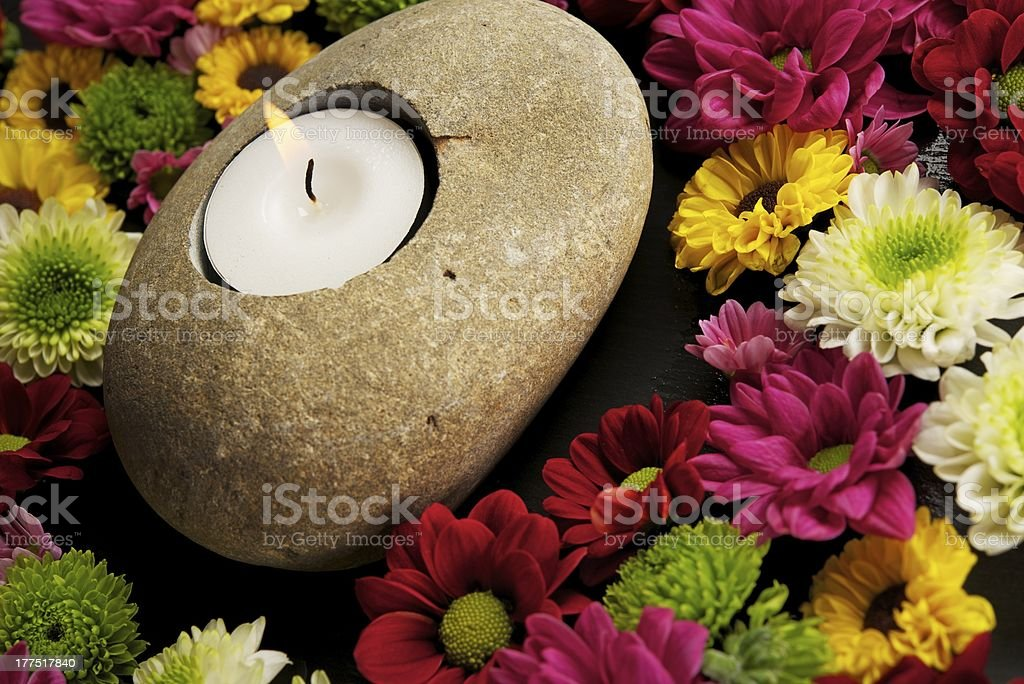 Candle with flowers around it royalty-free stock photo
