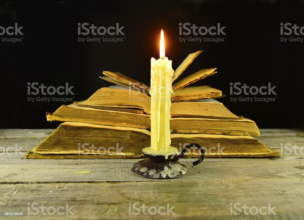 Candle with heap of books stock photo