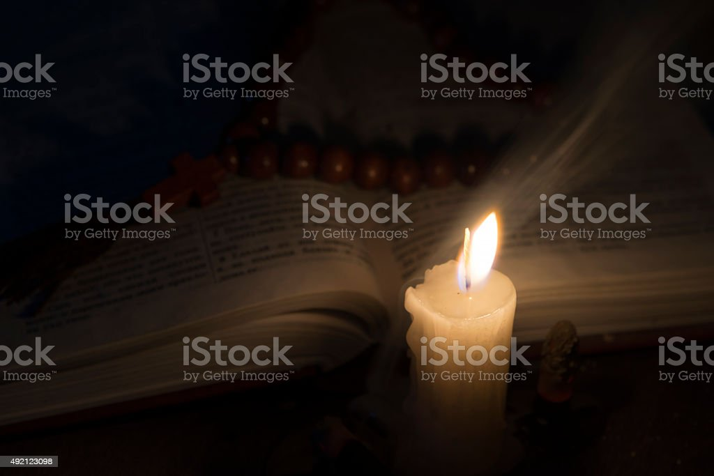 candle with incense and holy book stock photo