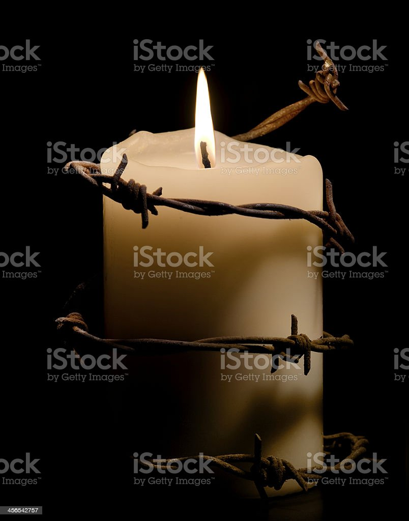 candle wrapped with barbed wire stock photo